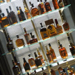 Bourbon bar display and storage of glass shelving, mirrored back-wall and a wide variety of bourbon