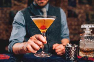 Bartender serving manhattan cocktails
