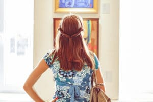 back view of young woman admiring paintings in art gallery