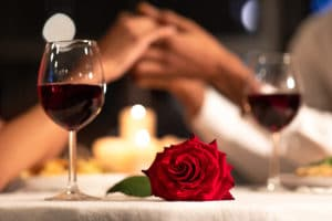 Romantic things to do in Bardstown KY, dining at a restaurant table with rose and red wine