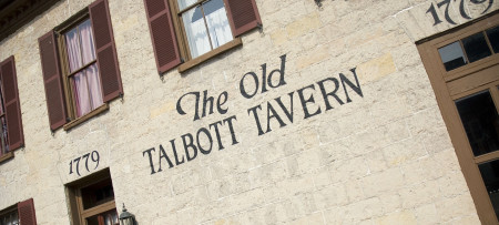The tan stone facade of The Old Talbott Tavern features four-pane windows with brown trim