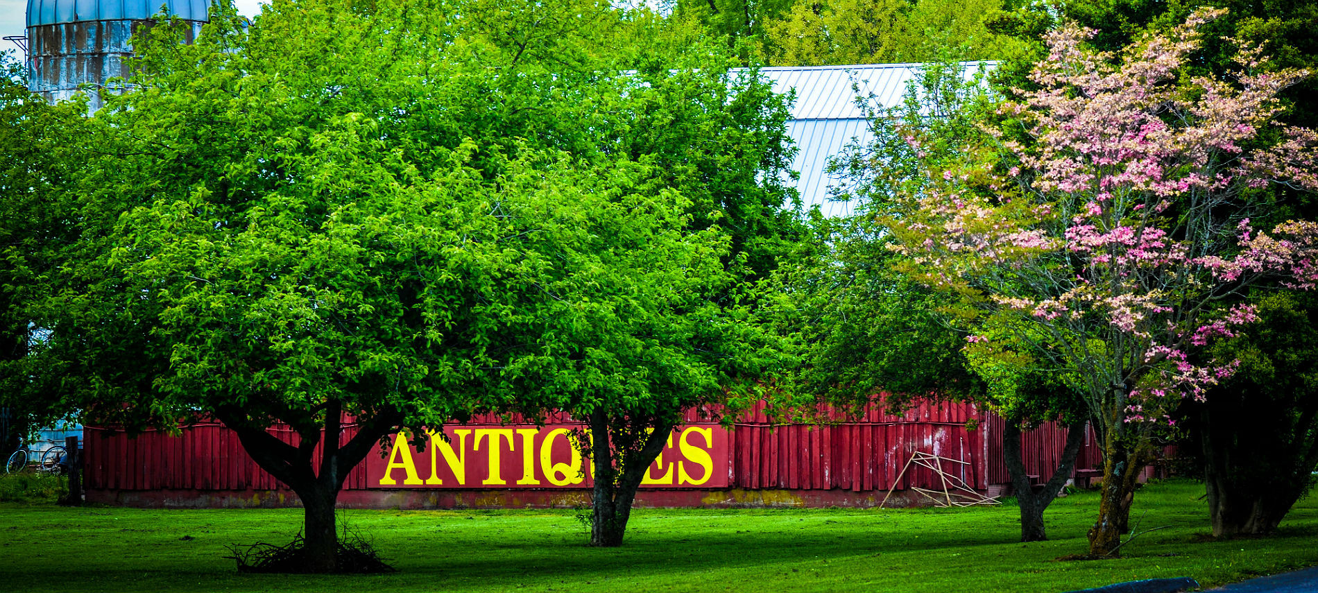 "A large red barn with ""Antiques"" displayed in large yellow letters behind lush green trees"