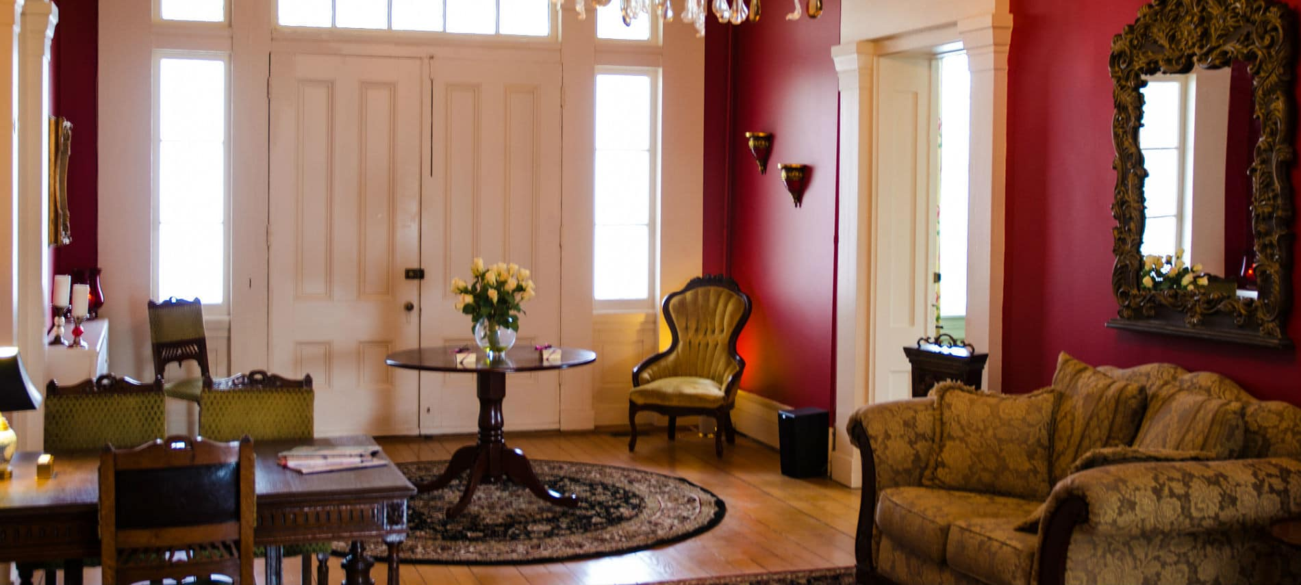 Gorgeous grand entryway with double doors, vaulted ceiling, scarlet walls, crystal chandelier and antique furnishings