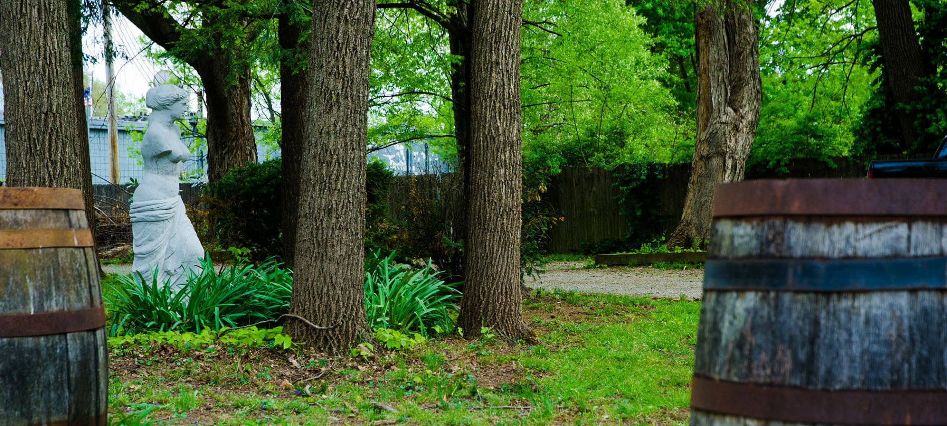 Bourbon Manor B&B grounds featuring mature trees, Venus di Milo statue in lush greenery and bourbon barrels
