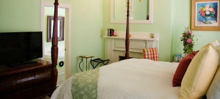 Cheerful guestroom with pale mint walls, white trim, light-colored stained-glass window, large mirror, chandelier and white bedding
