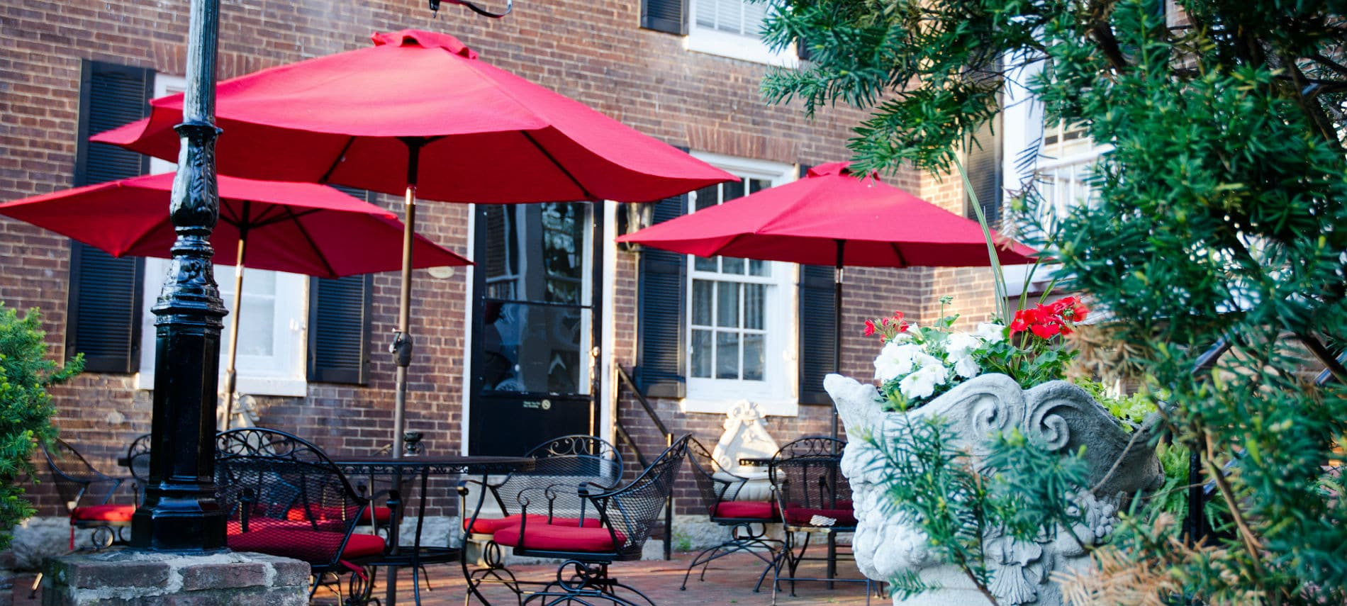 An inviting brick patio featuring black metal patio tables and chairs with scarlet umbrellas and cusions and cheerful planters