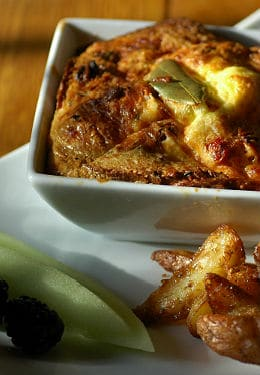 A delicious breakfast of a savory souffle, breakfast potatoes, sausage, blackberries and melon