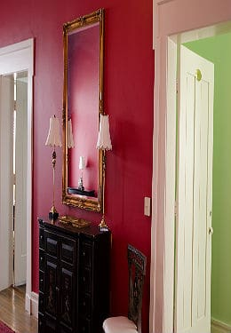 Hallway with scarlet walls, dark ornate cabinet, large gilded mirror and open guestroom doors