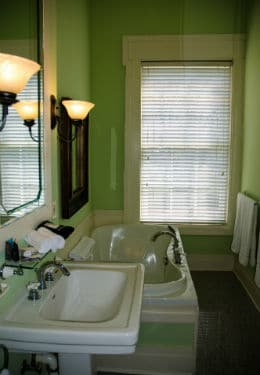 Bathroom with green walls, white trim, white jetted soaking tub, white sink and large mirror