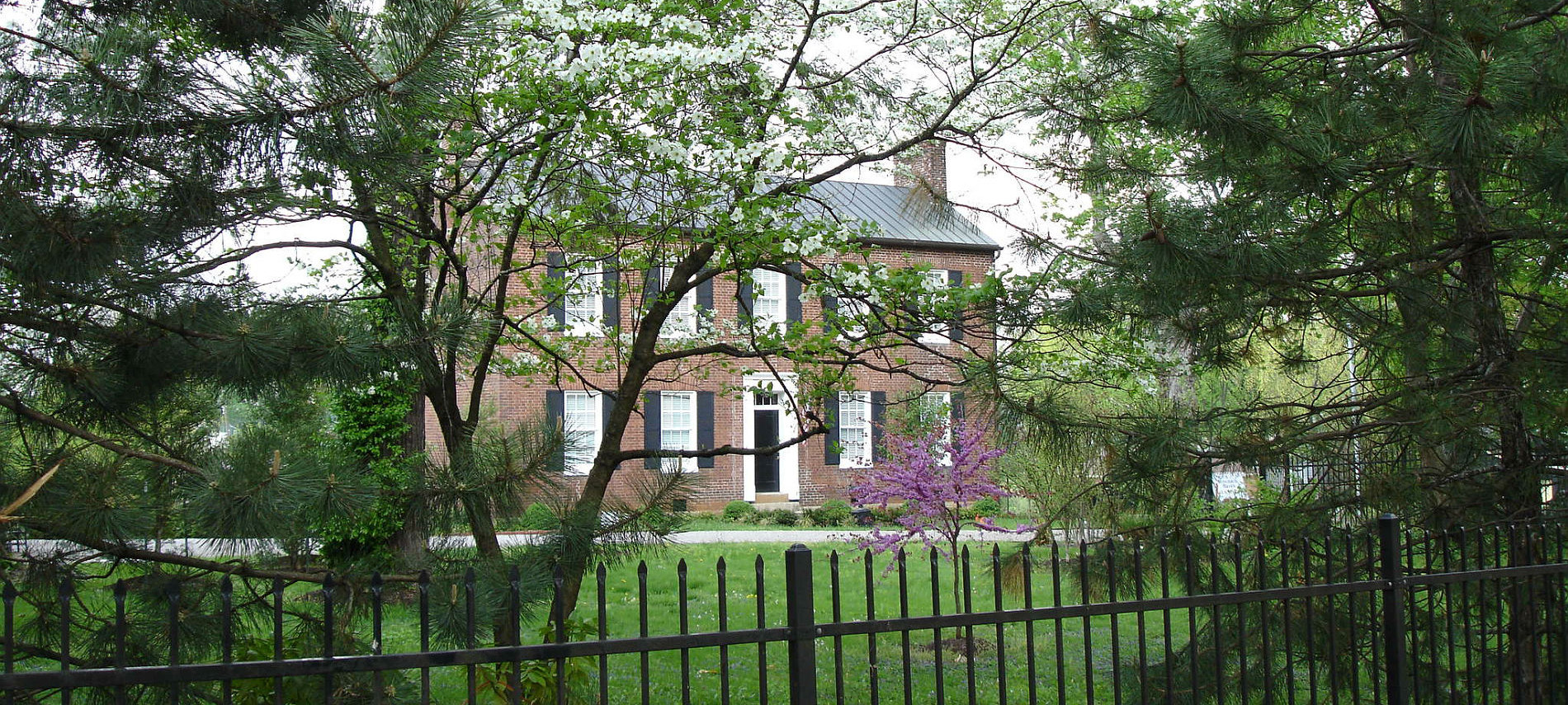 Springtime view of Bourbon Manor B&B's two-story brick Federal House with pine, dogwood and redbud trees in the foreground